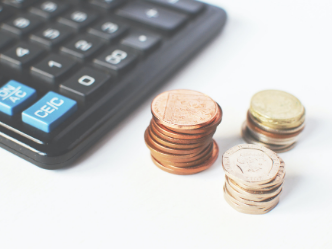A calculator and coins to count the price of payroll